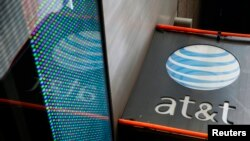 FILE - The signage for an AT&T store is seen in New York, Oct. 29, 2014. AT&T is one of the world's pioneering telecommunications companies, whose roots go back to the invention of the telephone in 1879.