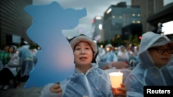 A woman holds a blue-colored cutout of the Korean Peninsula, symbolizing the unification of the two Koreas, during a candlelight vigil wishing for a successful summit between the U.S. and North Korea, in front of the U.S. embassy in Seoul, South Korea, June 9, 2018.