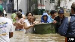 Cư dân tỉnh Bulacan, Philippines lội qua khu vực lụt lội vì bão Nalgae, ngày 3/10/2011