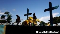 Dua wanita berjalan di samping makam orang yang meninggal akibat COVID-19 di pemakaman Parque Taruma di Manaus, Brazil, 20 Mei 2021. (Foto: REUTERS/Bruno Kelly)