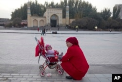 In this Nov. 4, 2017, a woman tends to her child near the Id Kah Mosque in Kashgar in western China's Xinjiang region. (AP Photo/Ng Han Guan)