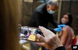 Dokter Anil Mehta tengah menyuntikkan vaksin COVID-19 produksi AstraZeneca kepada seorang tunawisma di akomodasi tunawisma YMCA di Romford, London timur, Rabu, 3 Februari 2021.