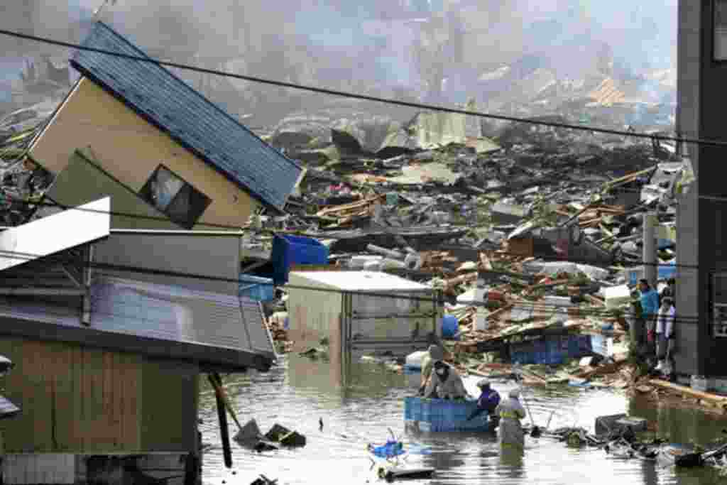 People, in a floating container, are rescued from a building following an earthquake and tsunami in Miyagi Prefecture, northeastern Japan March 12, 2011. Japan confronted devastation along its northeastern coast on Saturday, with fires raging and parts of