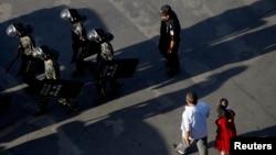2011年8月2日在新疆喀什一個廣場上﹐一個維吾爾族家庭在武警官兵旁邊走過。