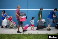 Residents carry their belongings into a shelter ahead of the landfall of Hurricane Irma in Estero, Fla., Sept. 9, 2017.