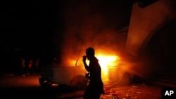 """2012年9月21日,数百名利比亚平民、军人和警察突袭了利比亚班加西""""安萨尔伊斯兰教义组织""""基地后,一个平民看着燃烧的汽车。资料照片"""
