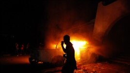 FILE - A Libyan civilian watches one of Ansar al-Shariah Brigades cars on fire, after hundreds of Libyans, Libyan Military, and Police raided the Brigades base, in Benghazi, Libya, Sept. 21, 2012.