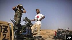 反卡扎菲的一名战士在开赴前线时用望远镜观察