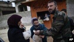 Una mujer pide a un miembro del Ejército Libre Sirio que le venda pan cerca de la ciudad de Idlib, en el noroeste de Siria.