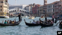 FILE - Tourists crowd the Grand Canal on traditional Gondola Venetian boats, in Venice, Italy, Sept. 28, 2014.