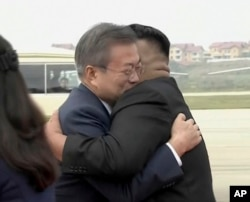 Image made from video provided by Korea Broadcasting System (KBS), South Korean President Moon Jae-in (L) hugs North Korean leader Kim Jong Un upon arrival in Pyongyang, North Korea, Sept. 18, 2018.