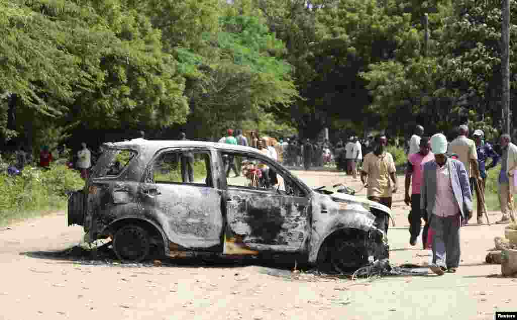 People walk past the wreckage of a car destroyed when gunmen attacked the coastal Kenyan town of Mpeketoni, June 18, 2014.