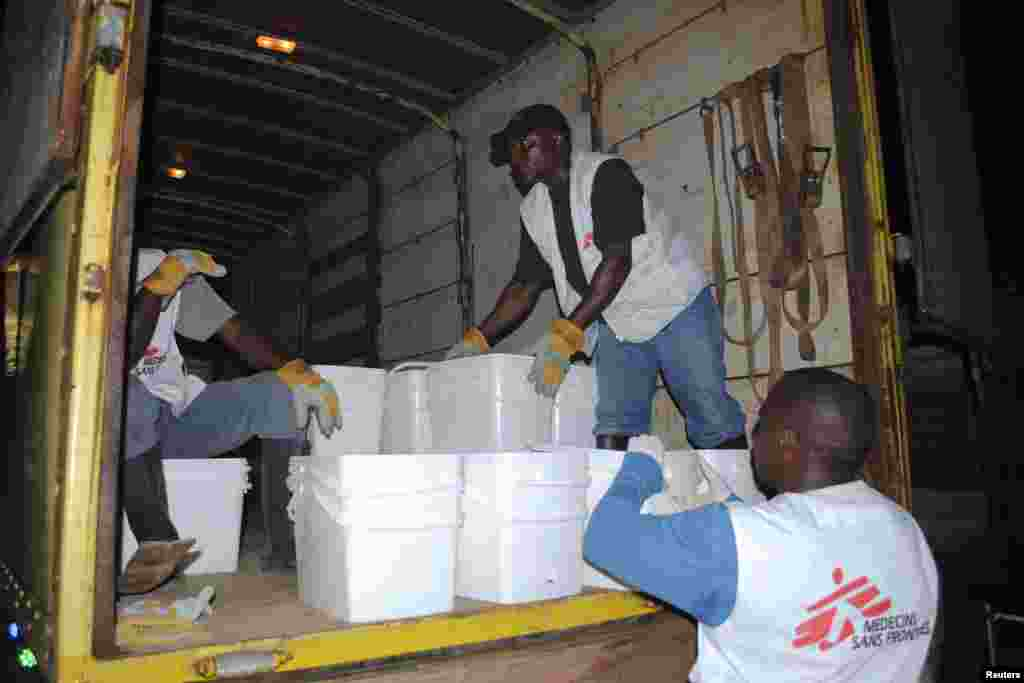 Workers for Doctors Without Borders distribute home disinfectant kits to prevent Ebola in Monrovia, Liberia, Oct. 20, 2014.
