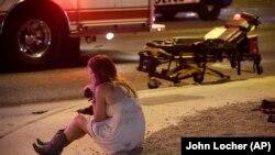 A woman sits on the street at the scene of a shooting outside of a music festival along the Las Vegas Strip. Months after Facebook and Google announced major efforts to curb the spread of false stories pretending to be news, it's still a problem, most rec