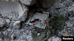 A bloodstained Syrian banknote is pictured at the site of a busy marketplace in the Douma neighborhood of Damascus. The market was hit by missiles Oct. 30, 2015.