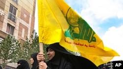一位女示威者高举黎巴嫩激进组织真主党旗帜。