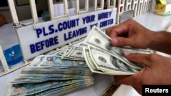 A worker counts U.S. dollar bills and Philippine pesos inside a money changer in Manila.