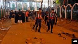 Petugas keamanan Bangladesh memeriksa lokasi ledakan bom di Dhaka, Bangladesh (24/10).