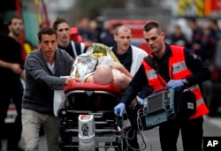 An injured person is evacuated outside the French satirical newspaper Charlie Hebdo's office, in Paris, Jan. 7, 2015.
