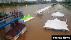 5일 오전 서울 중랑구 중랑천 장안교 밑에서 소방관들이 폭우로 인해 물에 떠내려가는 가건물을 교각 부근에 고정시키고 있다.