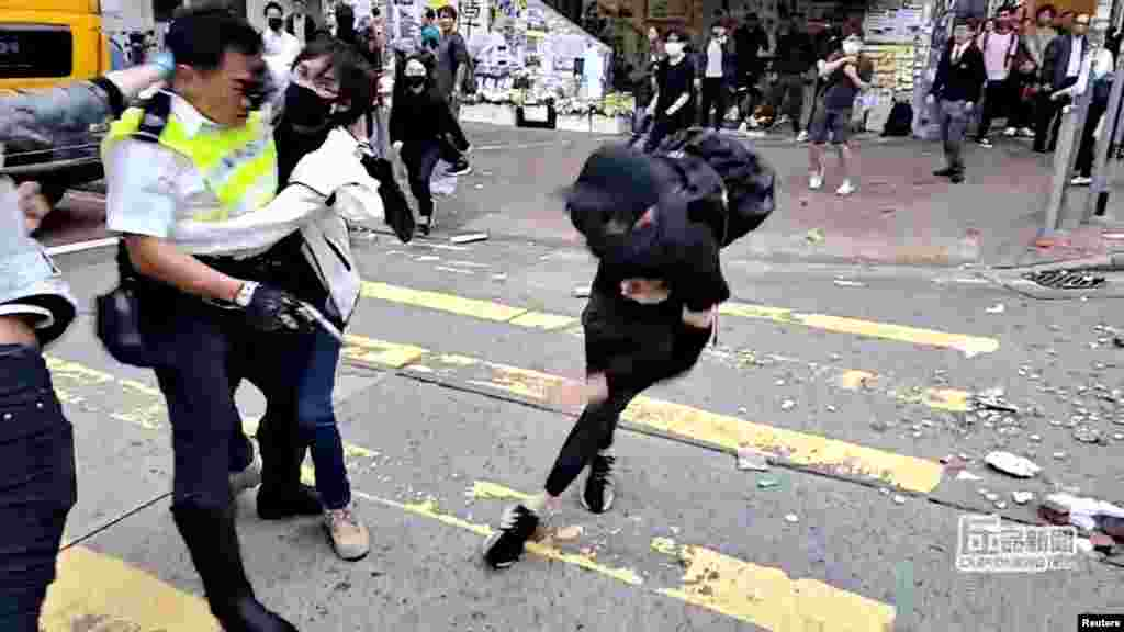 A still image from a social media video shows a protester try to prevent a police officer from aiming his gun at a protester in Sai Wan Ho, Hong Kong.