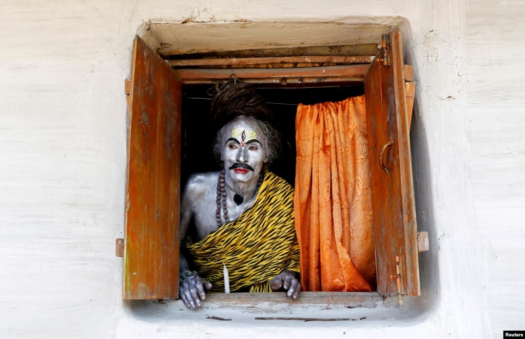 A devotee, dressed as Hindu God Shiva, looks out from a window as he waits to perform during the annual Shiva Gajan religious festival on the outskirts of Agartala, India.