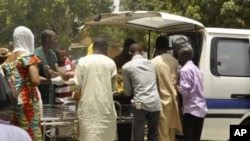 當地官員星期天在尼日利亞北方城市卡諾從巴士中搬出屍體﹐運往醫院