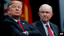 FILE - President Donald Trump sits with Attorney General Jeff Sessions during the FBI National Academy graduation ceremony in Quantico, Va., Dec. 15, 2017. Trump's White House counsel personally lobbied Attorney General Jeff Sessions to not recuse himself from the Justice Department's investigation into potential ties between Russia and the Trump campaign, according to sources.