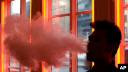 FILE - A patron exhales vapor from an e-cigarette at the Henley Vaporium in New York