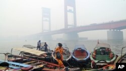 FILE - A woman disembarks from a boat as the Ampera Bridge is shrouded in haze from wildfires in Palembang, South Sumatra, Indonesia.