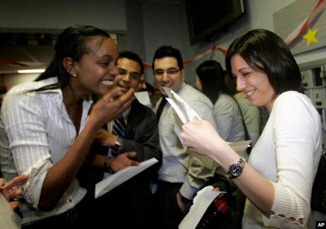 FILE - Boston University medical students Miriam Shiferaw, left, and Nawal Momani check letters together to find out where they have been accepted for their residency during Match Day at Boston University Medical School in Boston, March, 15, 2007. According to this year's data, of 42,000 applicants vying for residencies, all but about 6,000 are foreign nationals.