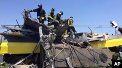 Italian firefighters search among debris at the scene of a train accident after two commuter trains collided head-on near the town of Andria, in the southern region of Puglia, killing several people, July 12, 2016.