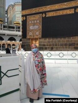 """Ata Faridah di depan Ka'bah. Jemaah tidak bisa menyentuh Ka'bah karena dikelilingi pagar. """"Begitu dekat tetapi tidak bisa menyentuh."""" (Foto: Ata Faridah/Pribadi)"""