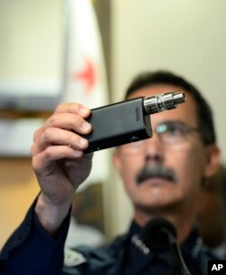 FILE - El Cajon Police Department Capt. Jeffery Davis holds up a vape device similar to the one that they claim that Alfred Olango was holding when he was shot, in El Cajon, Calif., Sept. 30, 2016.