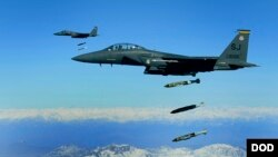 FILE - U.S. Air Force F-15E Strike Eagle aircraft from the 335th Fighter Squadron drop 2,000-pound joint direct attack munitions on a cave in eastern Afghanistan, Nov. 26, 2009.