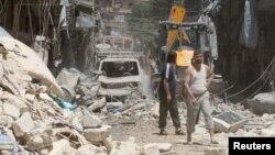 Warga menginspeksi daerah yang terkena serangan udara di daerah Al-Mashad, Aleppo, Suriah Selasa (26/7).