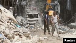 Cư dân tại một khu vực bị hư hại sau một cuộc không kích vào phiến quân, Syria, 26/7/2016.