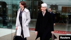 Head of the U.S. delegation, Under Secretary of State Wendy Sherman (R), and an unidentified person leave a hotel in Vienna, Feb. 17, 2014.