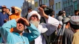 Warga menyaksikan mayat seorang penculik yang digantung dengan derek di kota Herat, Afghanistan Sabtu (25/9) lalu.