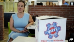 FILE - Christina Hernandez, an official with Organize Now, spends time at the Valisa Bakery to register voters in Orlando, Fla., Oct. 4, 2016. Organize Now is a progressive, grassroots nonprofit that is part of a coalition of groups working on registering