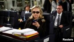 Hillary Clinton memeriksa ponselnya dalam perjalanan dinasnya sebagai Menlu AS dari Malta ke Libya tahun 2011 (foto: dok).
