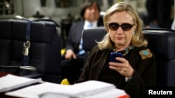 FILE - Then U.S. secretary of state Hillary Clinton checks her mobile phone aboard a C-17 military plane, Oct. 18, 2011.