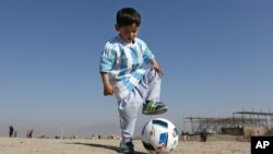 Murtaza Ahmadi, a 5-year-old Afghan Lionel Messi fan plays with a soccer ball. He and his family recently moved to Pakistan due to safety concerns.