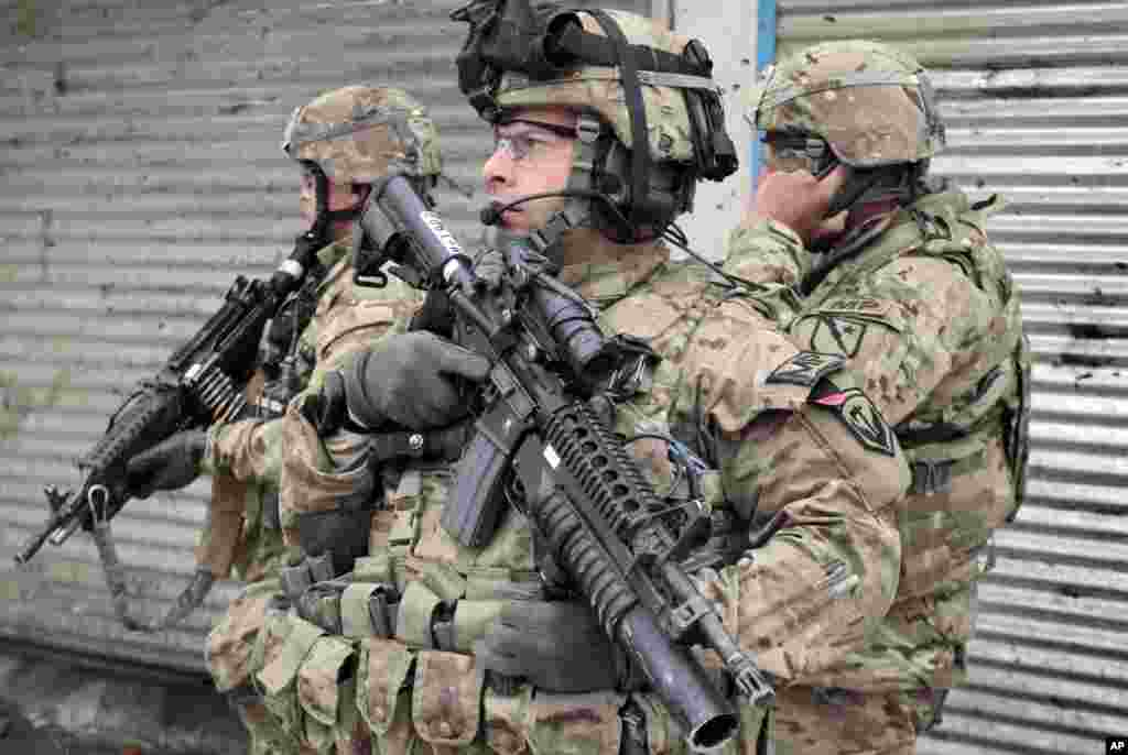 U.S. soldiers stand guard at the scene of a suicide attack in Kabul, Afghanistan, Feb. 27, 2013.