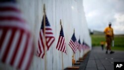 FILE - A visitor to the Flight 93 National Memorial pauses at the Wall of Names containing the names of the 40 passengers and crew of United Flight 93 that were killed in this field on Sept. 11, 2001, near Shanksville, Pennsylvania, May 31, 2018.