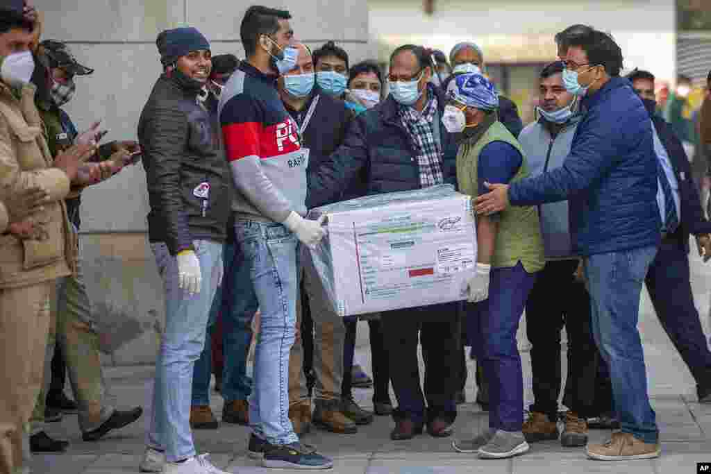 Health workers shift a box containing COVID-19 vaccine from a vehicle to a cold storage at Rajiv Gandhi Super Speciality hospital in New Delhi, India.