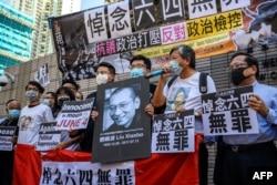 壹传媒集团创办人黎智英(左三)和香港支联会成员以及支持者在西九龙法院应讯前手举刘晓波遗像和悼念六四无罪的牌子呼喊口号。(2020年7月13日)(2020年7月13日)