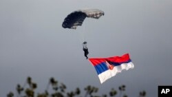 FILE - A Serbian army paratrooper descends with a giant Serbian flag during a military parade in Belgrade, Serbia, Oct. 16, 2014.