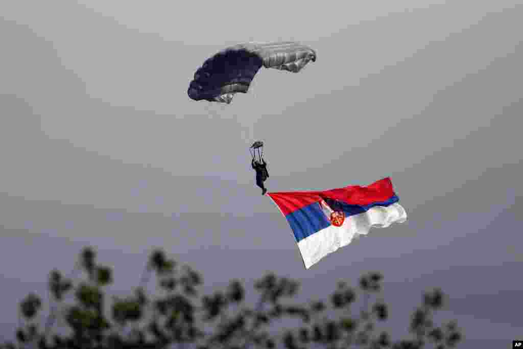 A Serbian army paratrooper descends during a military parade in Belgrade. Tens of thousands came to see the parade in Belgrade attended by Vladimir Putin, which marked the 70th anniversary of the liberation of the Serbian capital from the Nazi German occupation.