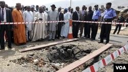 Presiden Nigeria Goodluck Jonathan (tengah, bertopi hitam) mengunjungi gereja Katholik St. Theresa yang terkena serangan bom pada hari Natal, di pinggiran ibukota Abuja (31/12).